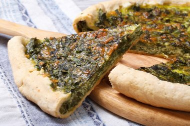 Piece of pie with green spinach, eggs and cheese