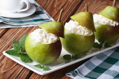 Fresh pears stuffed with cottage cheese closeup on table