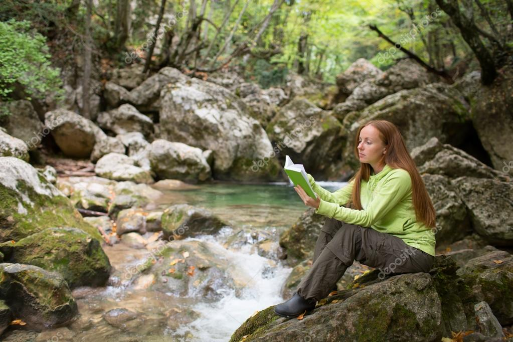 Girl with book near river