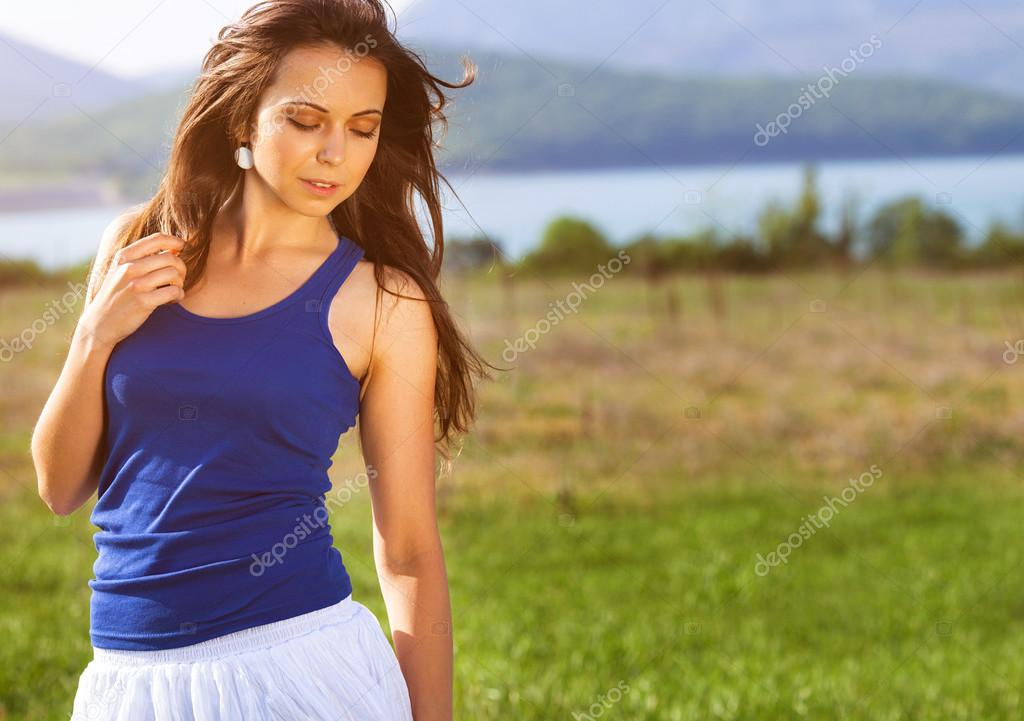 Beautiful girl posing on the summer field