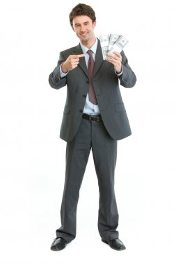 Smiling businessman pointing on packs of dollars