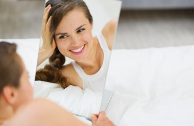 Happy young woman laying on bed and looking on mirror