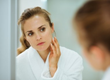 Young woman in bathrobe checking her face in mirror in bathroom