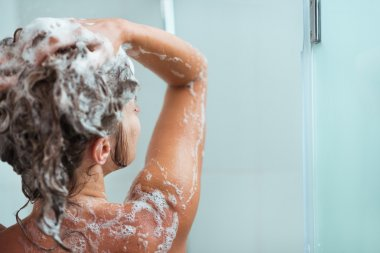 Woman applying shampoo in shower. Rear view