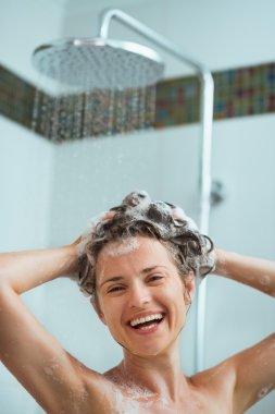 Happy woman applying shampoo in shower