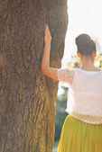 Photo Young woman lean against tree. Rear view
