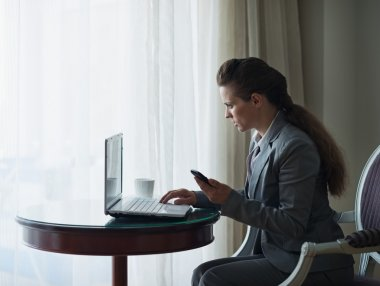 Business woman working on laptop in hotel room