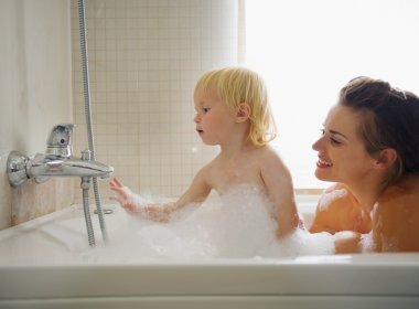 Mother and baby playing in bathtub