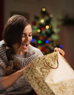 Happy woman in front of Christmas tree looking in shopping bag