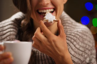 Closeup on happy woman eating Christmas cookie in front of Chris