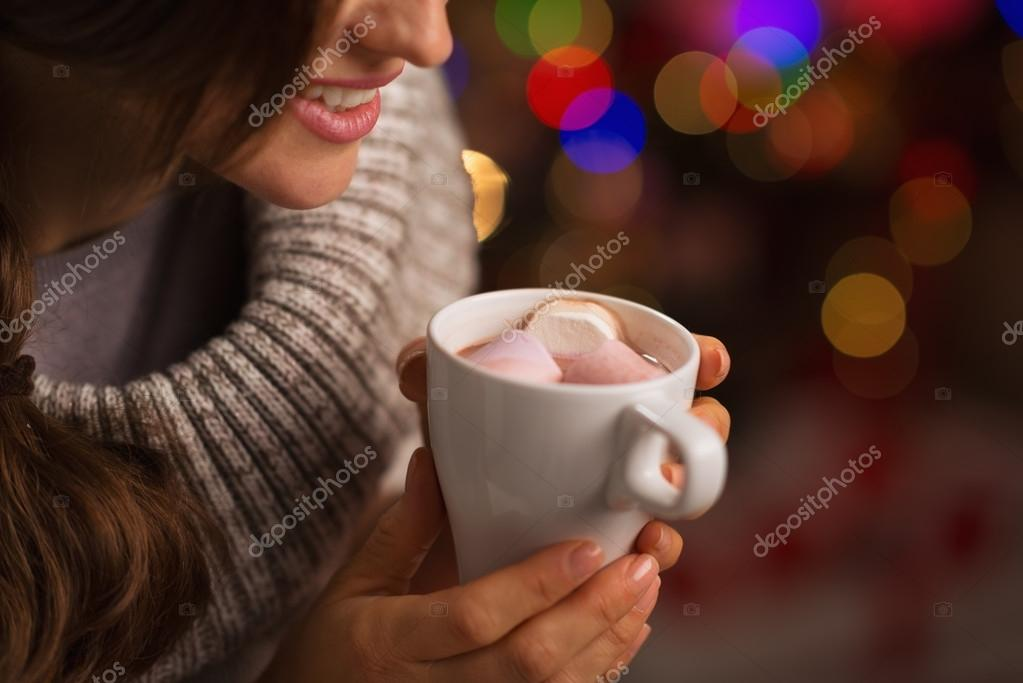 Closeup on hot chocolate with marshmallows in hand of happy woma