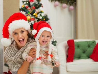 Portrait of mom and eat smeared baby girl in Christmas hats near