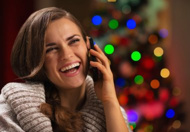 Smiling young woman speaking mobile phone in front of Christmas