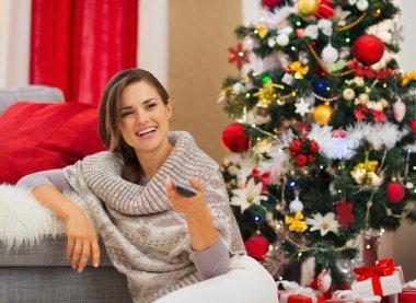 Happy woman watching TV near Christmas tree