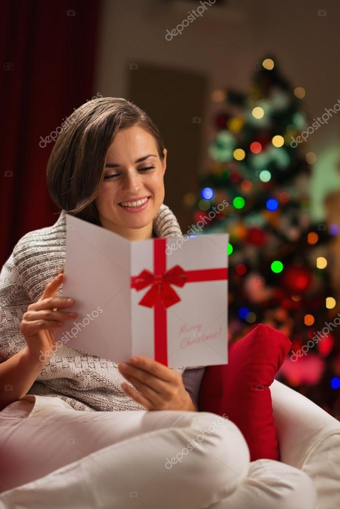 Happy young woman reading Christmas postcard