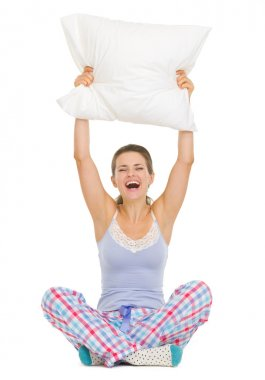 Young woman in pajamas sitting and holding pillow