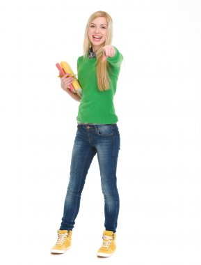Full length portrait of happy student girl pointing in camera