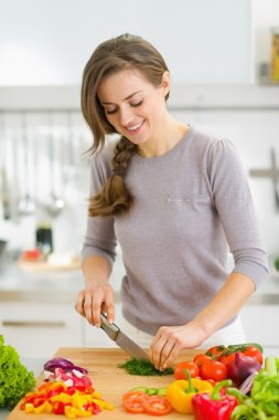 Happy young housewife cutting fresh dill in kitchen