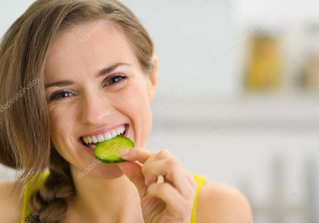 Happy young woman eating slice of cucumber