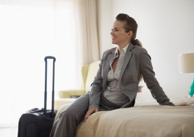 Smiling business woman sitting on bed in hotel room