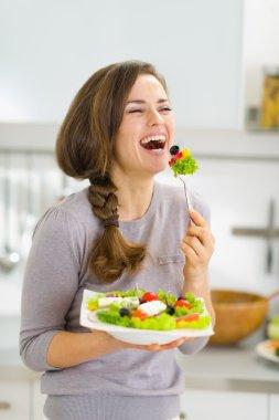 Happy young woman eating fresh salad