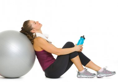 Tired fitness young woman relaxing after workout on fitness ball