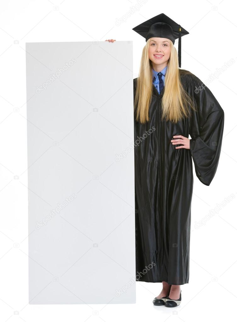 Full length portrait of smiling young woman in graduation gown s ...