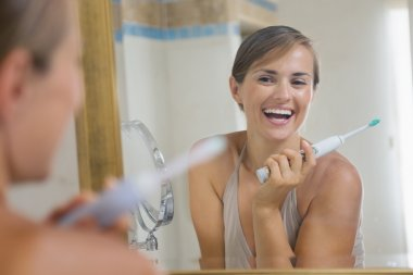 Happy young woman enjoying clean teeth after brushing electric t