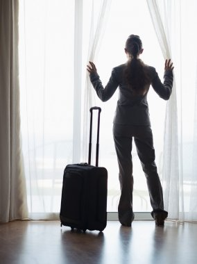 Silhouette of business woman with wheel bag looking into hotel window