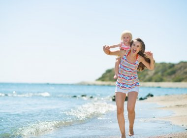 Happy mother holding baby on back and running along sea shore