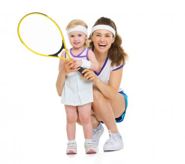 Portrait of happy mother and baby holding tennis racket