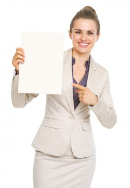 Happy business woman pointing on blank paper sheet