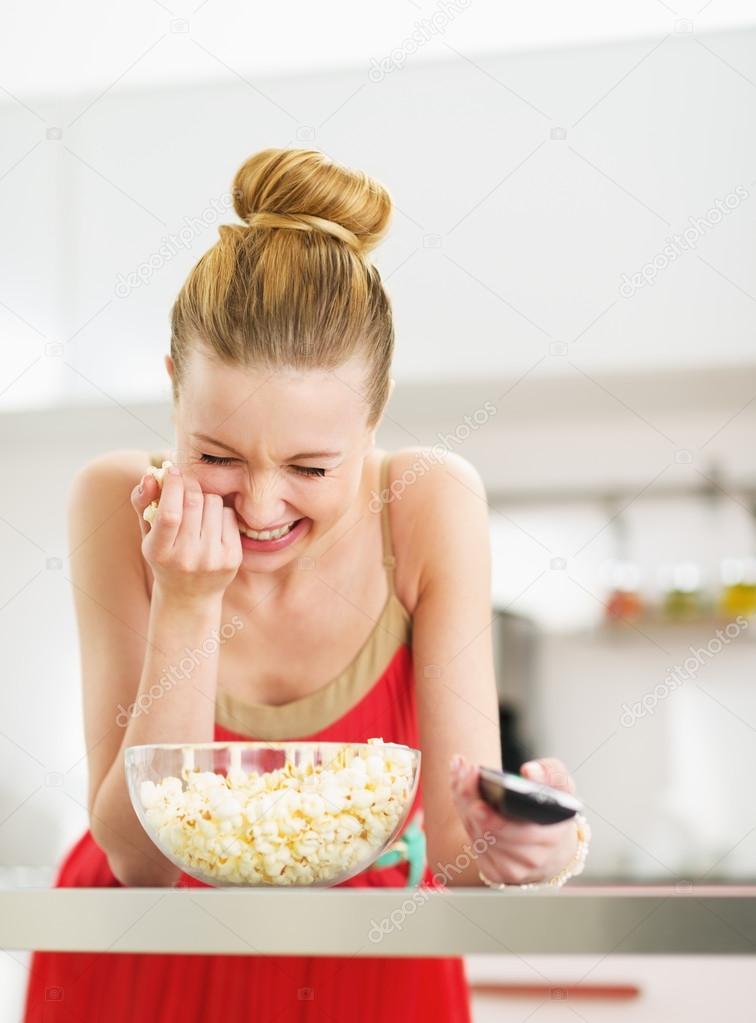 ridendo la giovane donna mangiare popcorn e guardare la tv in cucina ...