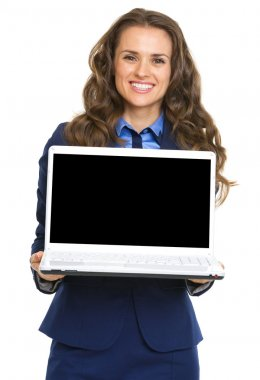 Smiling business woman showing laptop blank screen