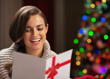 Smiling young woman reading christmas postcard in front of chris