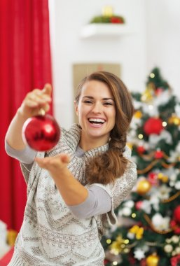 Happy young woman showing christmas ball