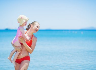 Smiling mother and baby on sea background looking on copy space
