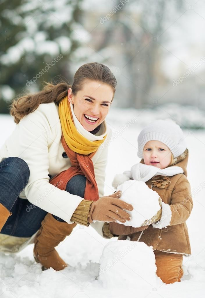 Happy mother and baby making snowman in winter park