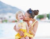 Fotografie Mutter küssen Baby beim Eis essen