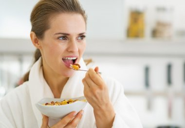 Young housewife in bathrobe having healthy breakfast in kitchen