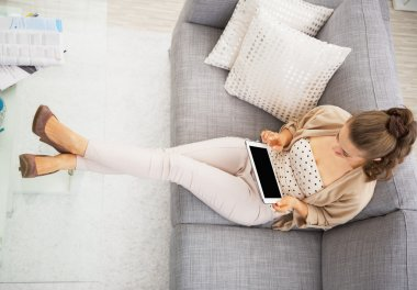 Young woman sitting on sofa with tablet pc
