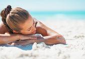 boldog, fiatal nő, fürdőruhát pihentető, miközben szóló, homokos bea