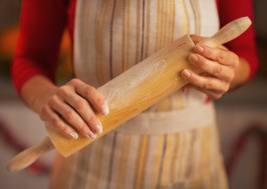 Closeup on young housewife holding rolling pin