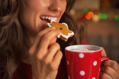 Closeup on young woman eating christmas cookie