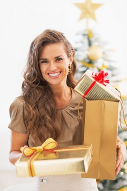 Young woman christmas present boxes in front of christmas tree