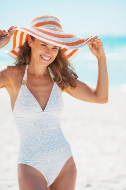 Portrait of happy young woman in swimsuit with beach hat