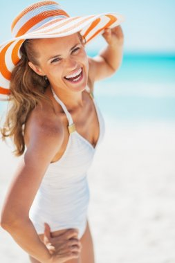 Smiling young woman in swimsuit and beach hat at seaside