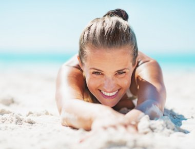 Happy young woman in swimsuit laying on sandy beach