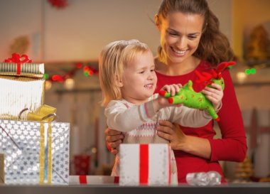Happy mother and baby opening christmas presents