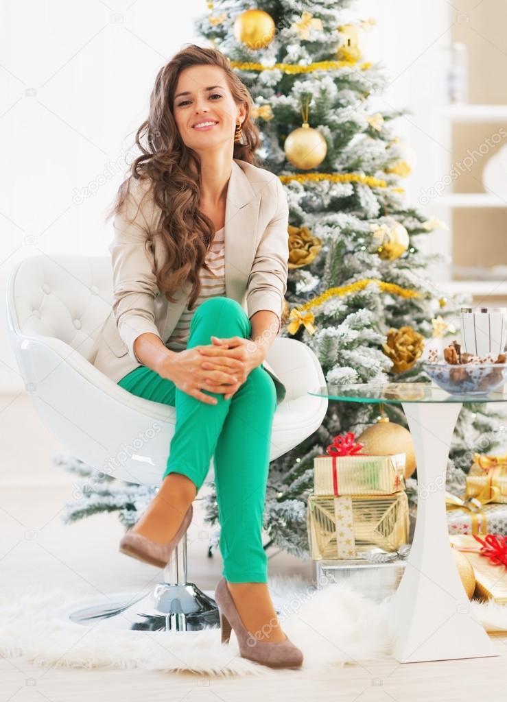 Modern young woman sitting near christmas tree